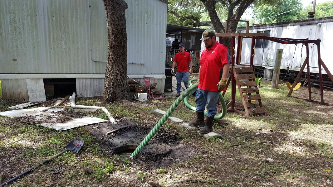 Maintenance staff clean up raw sewage outside an Oak Hollow home. - CITY OF SAN ANTONIO / RAY GARZA
