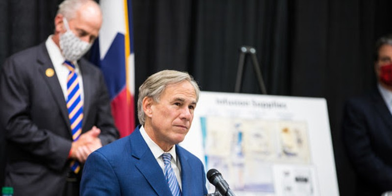 Gov. Greg Abbott shows off a chart explaining how higher death rates can slow the spread of the coronavirus.