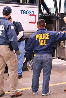 ICE agents arrest a suspect during a raid.