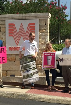 Luke Metzger (second from left) and other members of Environment Texas hold signs in front of Whataburger's S.A. headquarters.