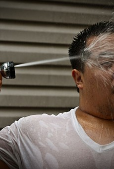A man seeks relief from the heat by blasting himself in the face with a garden hose.