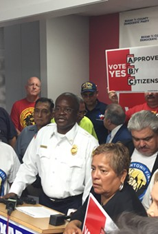 Chris Steele speaks at the Bexar County Democratic Party headquarters. That's not a real firefighters shirt he's wearing.
