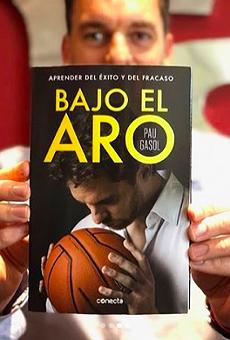 Pau Gasol shows off a copy of his autobiography, Bajo El Aro.