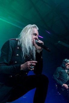 Saxon singer Biff Byford leans on the monitor while guitarist Paul Quinn unleashes a monster riff.