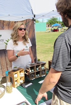 Carolyn Leeper of the Farmacy Botanical Shop discusses her product line at an outdoor mar- ket on the South Side.