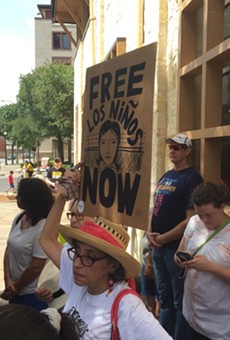 A woman listens to speakers at a San Antonio rally decrying the Trump administration's immigration policies.