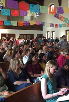 People at a San Antonio town hall on domestic violence listen to a survivor share  her story.
