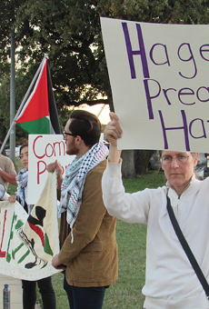 Protestors hold up signs and banners outside of Pastor John Hagee's Cornerstone Church.