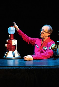 Host Joel Hodgson points out a movie's awfulness to his robot pals.
