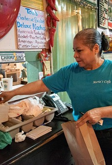 Maria Beza, owner of Maria's Cafe on Nogalitos Street, completes an order on Thursday.