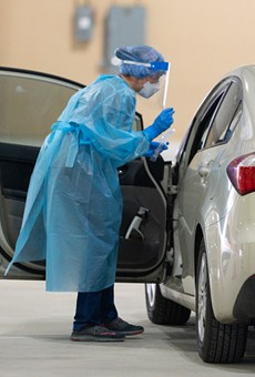 A worker at a drive-through testing facility in San Antonio prepares to collect a sample from someone in a vehicle.