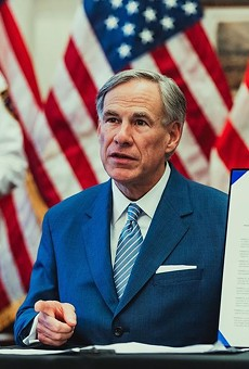 Gov. Greg Abbott shows off an executive order during a recent press conference.