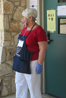 A poll worker stands outside the voting site at San Antonio's Lion's Field.