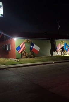 Local artist Ghost works through the night to complete a tribute mural in honor of deceased US Army soldiers Guillen and  Morales.