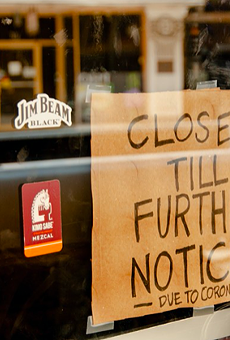 A homemade closure sign hangs in the window of a downtown San Antonio business.