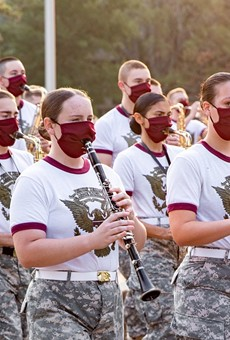 Members of the Aggie Band march through the Texas A&M campus while wearing masks.