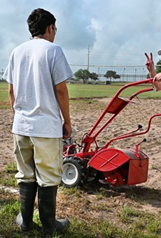 A horticulture teacher shows a youth at a TJJD facility how to safety start a garden tiller.