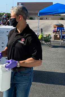 Mayor Ron Nirenberg helps hand out sanitizer to small businesses during an event this summer.