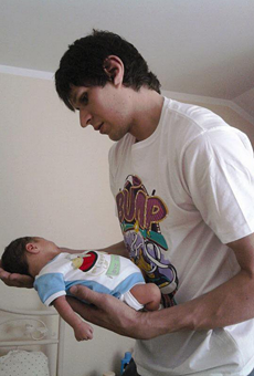 Boban Marjanović holding a baby with his enormous hands.