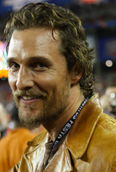 Matthew McConaughey flashes the hook 'em horns sign at a UT football game.