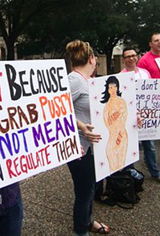 Planned Parenthood supporters hold signs at a San Antonio rally in 2017.