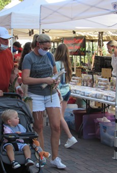 Visitors to the Pearl's weekend farmer's market in San Antonio wear masks as they stroll among the vendors.
