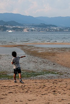 A child plays next to a lake.