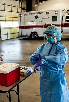 A medic pulls on gloves as she gets ready to work at a mobile testing site in the Texas Hill Country.