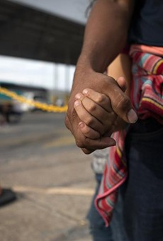 A Honduran asylum seeker holds his daughters' hand at an immigration checkpoint in Nuevo Laredo. The pair were promptly returned to Mexico to await a court hearing under the Migrant Protection Protocols.