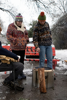 From left: Martin Xoxa, Chelsea Pursley and Joe Williams build a fire on Thursday to keep warm outside of Pursley's home in East Austin. The group had been without power since Monday evening.
