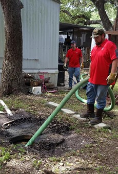 Maintenance staff clean up raw sewage outside an Oak Hollow home.