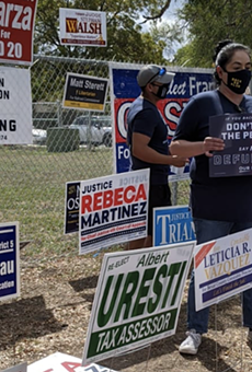 Opponents of Fix SAPD's petition drive hold up signs at a polling site where volunteers collected signatures last fall.
