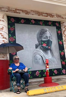 San Antonio based artist Kim Bishop's mother sits next to her daughter's mural outside of Jefferson Bodega.
