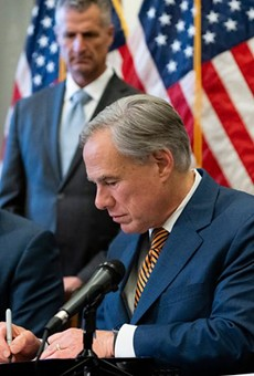 Gov. Greg Abbott signs bills at the Texas Capitol.