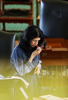 State Sen. Carol Alvarado, D-Houston, applies lipstick in her 15th hour of filibustering against Senate Bill 1.