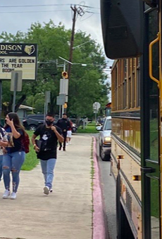 Masked students approach Thomas Edison High School.