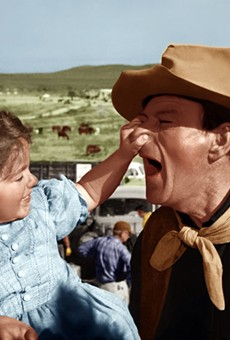 A young Aissa Wayne (left) photographed on set with her father.
