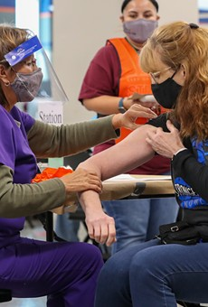 A woman receives her COVID-19 vaccination at the Alamodome.