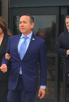 State Sen. Carlos Uresti leaves San Antonio's federal courthouse, followed by attorney Mikal Watts, after his May indictment.