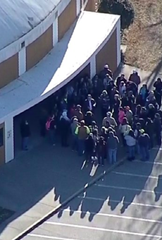 Parents gather outside of an Italy High School building Monday morning.