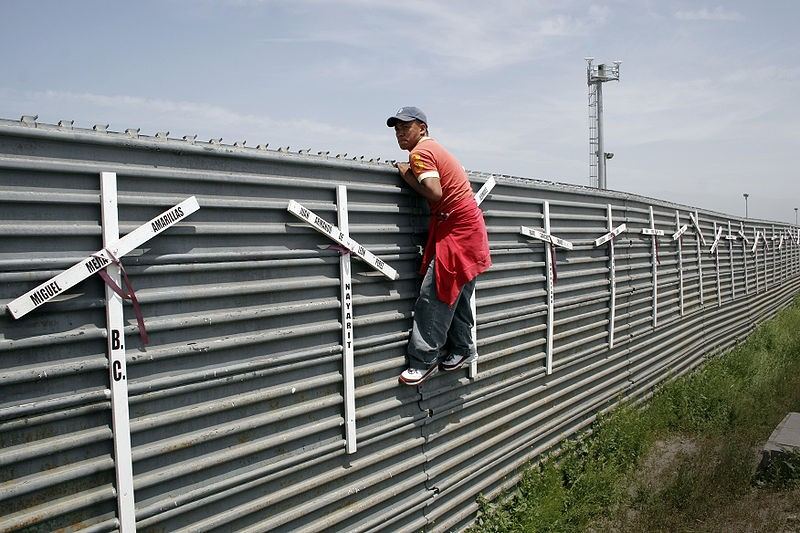 An aspiring migrant scales a fence to cross the U.S.-Mexico border. - WIKIMEDIA COMMONS