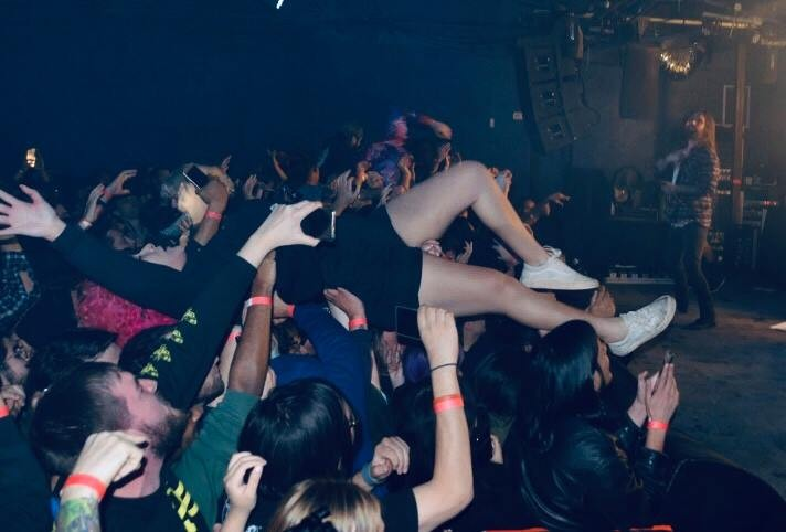 A girl lands in the crowd after stage diving as the lead singer from Every Time I Die rocks out. - CHRIS CONDE