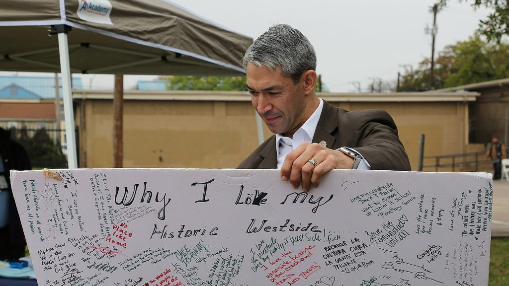 Mayor Ron Nirenberg reads a poster board at an Alazan Courts festival March 2. - BEN OLIVO / HERON