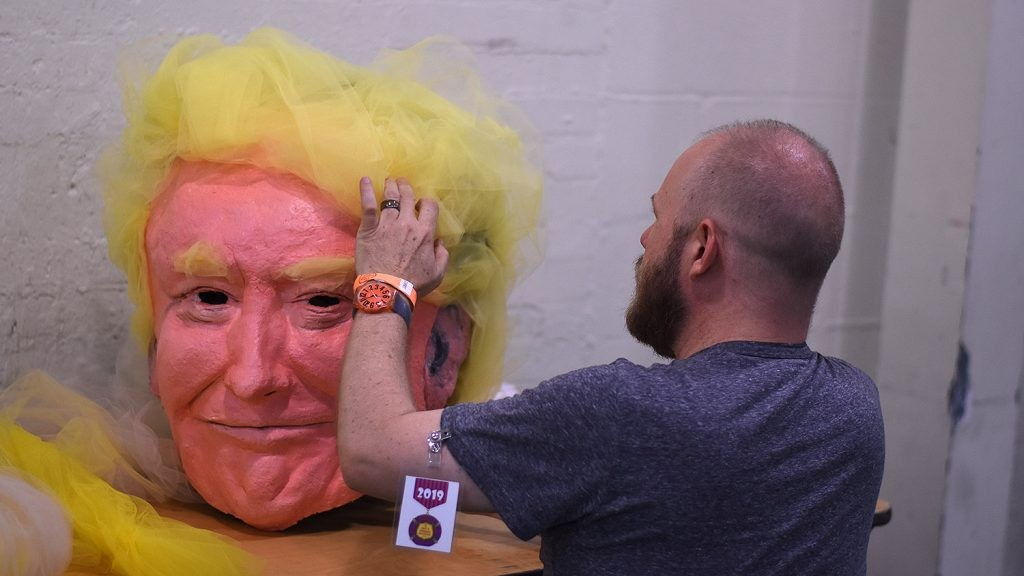 Chris Sauter touches up a papier-mâché version of President Donald Trump back stage Tuesday night at the Empire Theatre. - JACK MYER
