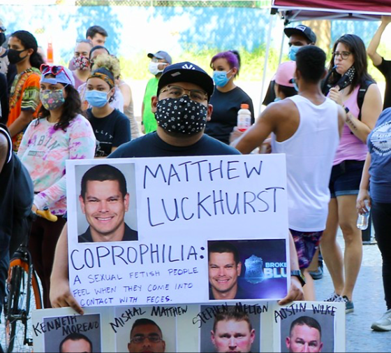 A protester at a recent San Antonio anti-police brutality demonstration holds up a sign showing fired officer Matthew Luckhurst's photograph. - JAMES DOBBINS