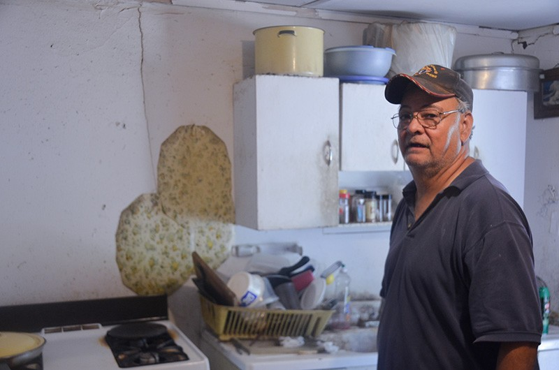 Robert Crain stands in the kitchen of the dilapidated home he shares with his mother, Margaret. - MICHAEL MARKS