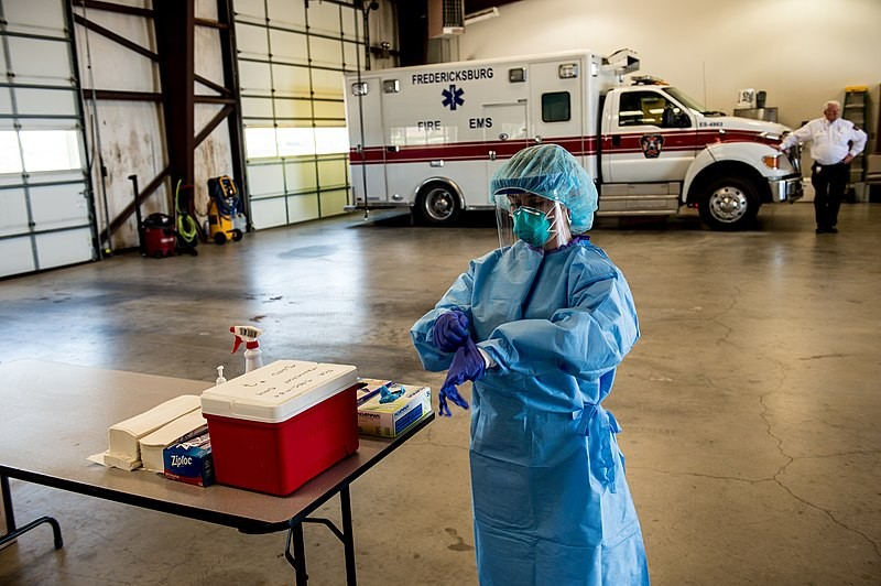 A medic pulls on gloves as she gets ready to work at a mobile testing site in the Texas town of Fredericksburg. - WIKIMEDIA COMMONS / CHARLES SPIRTOS