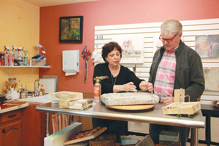 Michelle Belto explains the encaustic process to Gary Sweeney. - GARY SWEENEY