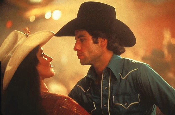 Travolta boot scoots with revenge-in-a-cowboy-hat, Pam.