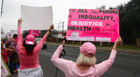 Protesters hold up signs at a pro-Planned Parenthood rally in San Antonio. - MICHAEL BARAJAS